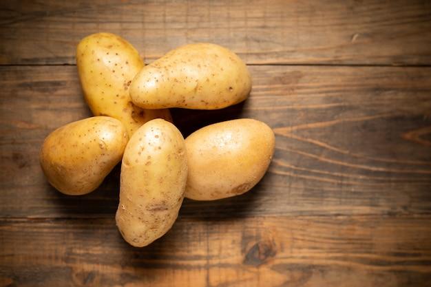 Rohe kartoffel auf hölzernem hintergrund. Kostenlose Fotos