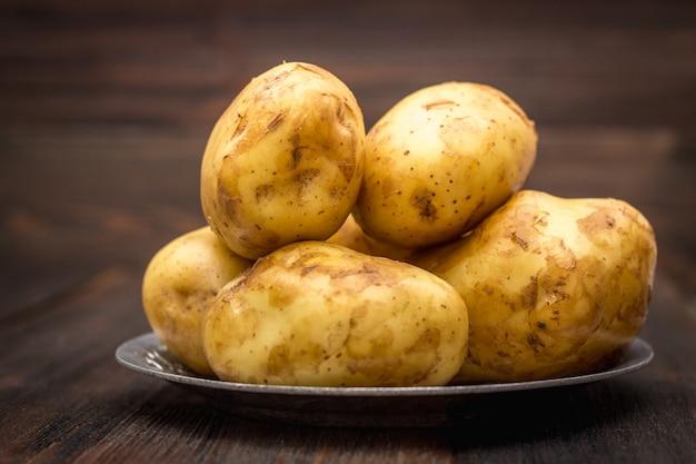 Rohe kartoffeln auf einem braunen hölzernen hintergrund Premium Fotos