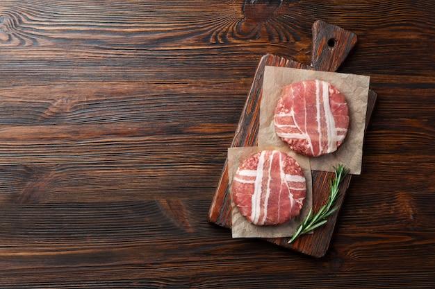 Rohe koteletts des hamburgers mit rosmarin auf schneidebrett und holztisch Premium Fotos