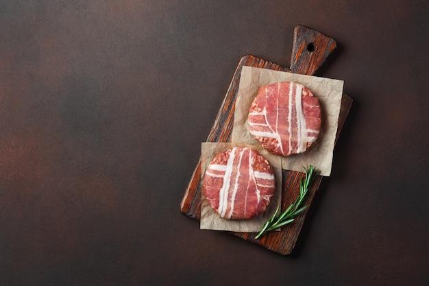 Rohe koteletts des hamburgers mit rosmarin auf schneidebrett und rostigem hintergrund Premium Fotos