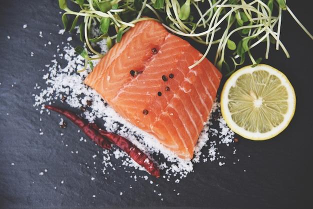 Rohe lachsfischmeeresfrüchte mit tomatenzitronenkräutergewürzen und sonnenblumensprössling Premium Fotos