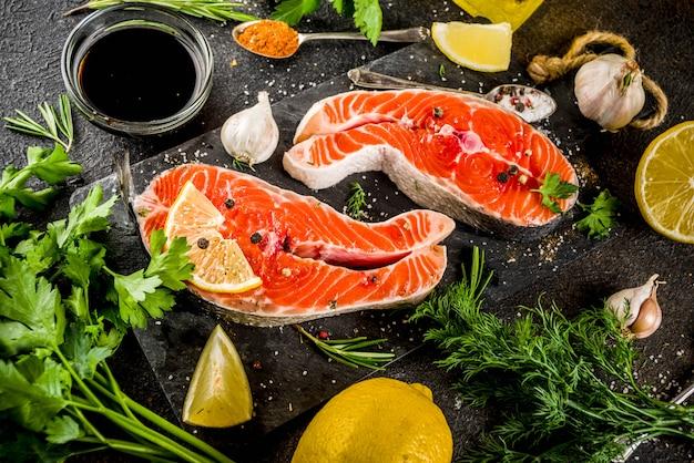 Rohe lachssteaks mit zitrone, kräutern, olivenöl, fertig zum grillen Premium Fotos
