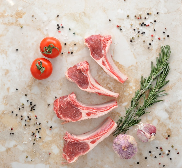 Rohe lammkoteletts mit rosmarin, knoblauch und tomate Premium Fotos