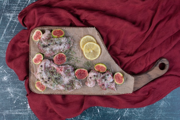 Rohe rippen in holzbrett mit feigen, getrockneten kräutern und rotem tuch. Kostenlose Fotos