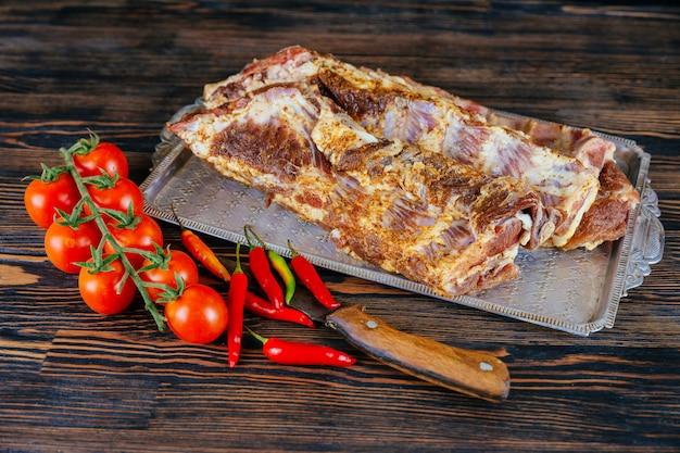 Rohe rippen mit gewürzen und gemüse. Premium Fotos