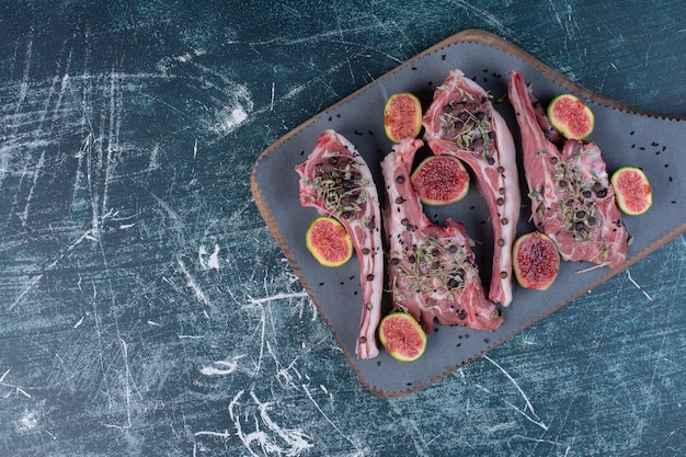 Rohe rippenkoteletts in holzbrett mit feigen und getrockneten kräutern. Kostenlose Fotos