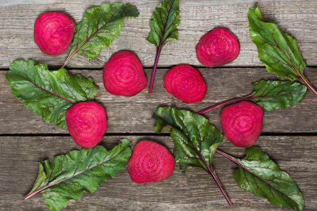 Rohe rote-bete-wurzeln geschnitten und mangold verlässt auf rustikalem brett beschneidungspfad eingeschlossen. Premium Fotos