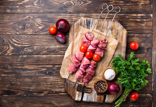 Rohe schaschlikaufsteckspindeln mit tomaten Premium Fotos