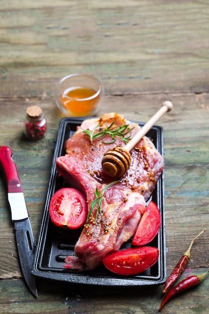 Rohe steaks und bratpfannen mit gewürzen, beilagen und zutaten auf dunkler, rustikaler rückseite Premium Fotos