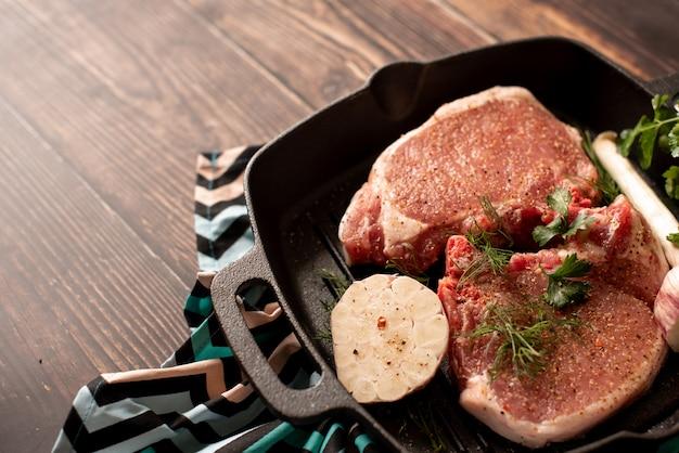 Rohe ungekochte lammfleischhiebe mit rosmarin und knoblauch in der schwarzen eisengrillwanne Premium Fotos