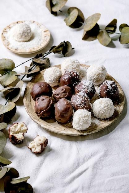 Rohe vegane hausgemachte kokosnuss-pralinenbällchen mit kokosflocken in der keramikplatte über weißem textilhintergrund mit eukalyptuszweigen Premium Fotos