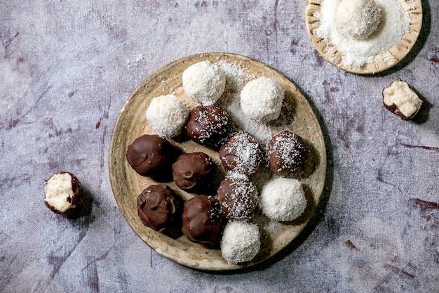 Rohe vegane hausgemachte kokosnussschokoladenbonbonkugeln mit kokosflocken in der keramikplatte über weißem hölzernem hintergrund Premium Fotos
