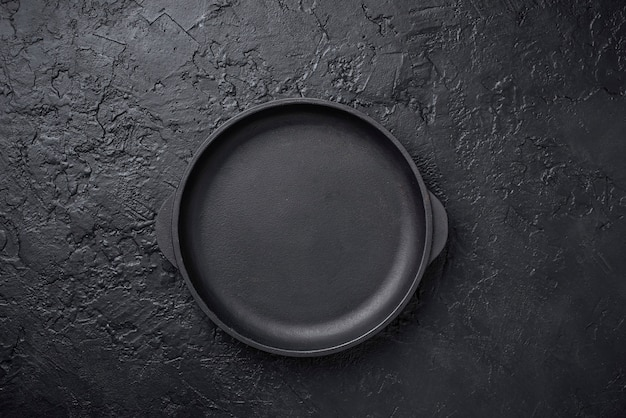 Roheisenbratpfanne auf schwarzem backgound Premium Fotos