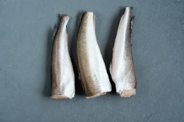 Roher fisch seehecht. fünf rohes fischfilet auf grau Premium Fotos