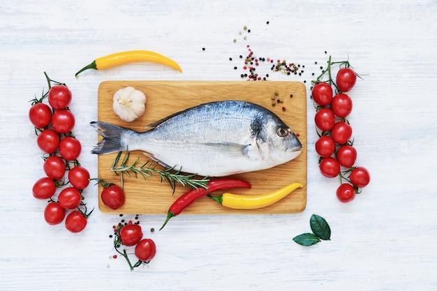 Roher frischer dorado-fisch mit gemüse und gewürzen. gesundes lebensmittelkonzept. draufsicht, kopierraum. mediterranes meeresfrüchte-konzept. Premium Fotos