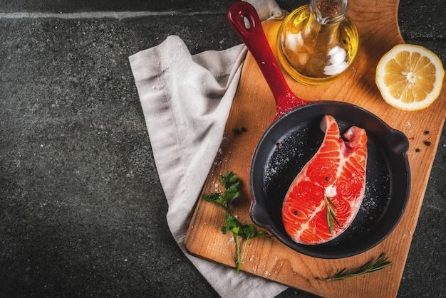 Roher frischer lachsfisch mit bestandteilen für das kochen des olivenöls, der zitrone, der zwiebel, der petersilie, des rosmarins, auf bratpfanne, schwarze steintabelle, draufsicht copyspace Premium Fotos