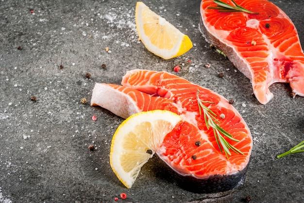 Roher frischer lachsfisch mit bestandteilen für das kochen des olivenöls, der zitrone, der zwiebel, der petersilie, des rosmarins, auf schwarzer steintabelle, copyspace Premium Fotos