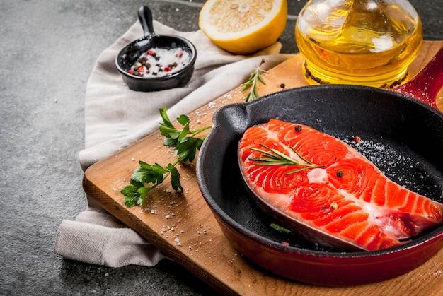 Roher frischer lachsfisch mit zutaten zum kochen - olivenöl, zitrone, zwiebel, petersilie, rosmarin, auf pfanne, schwarzer steintabelle, copyspace Premium Fotos