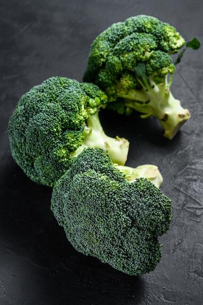 Roher grüner brokkoli auf einem schwarzen hintergrund. ansicht von oben Premium Fotos