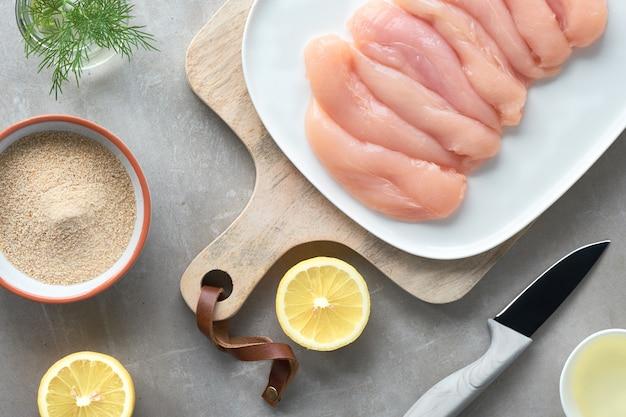 Rohes hähnchenfilet. fleisch mit paniermehlkräutern, zitrone und speiseöl. draufsicht auf licht Premium Fotos