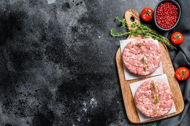 Rohes hühnchenpastetchen, hackfleischkoteletts auf einem schneidebrett. bio-hackfleisch. draufsicht. speicherplatz kopieren Premium Fotos