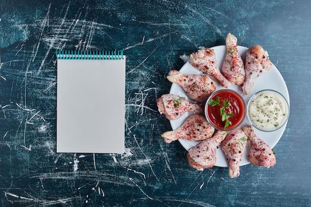 Rohes hühnerfleisch in einem weißen teller mit einem kochbuch beiseite. Kostenlose Fotos
