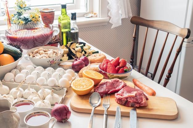 Rohes lebensmittel des bestandteiles mit dem gemüse und früchten, die für auf dem tisch kochen sich vorbereiten Premium Fotos