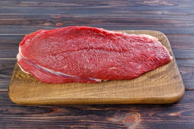 Rohes rindfleischfleisch: großes filet des frischen rindfleischschweines auf hölzernem brett Premium Fotos