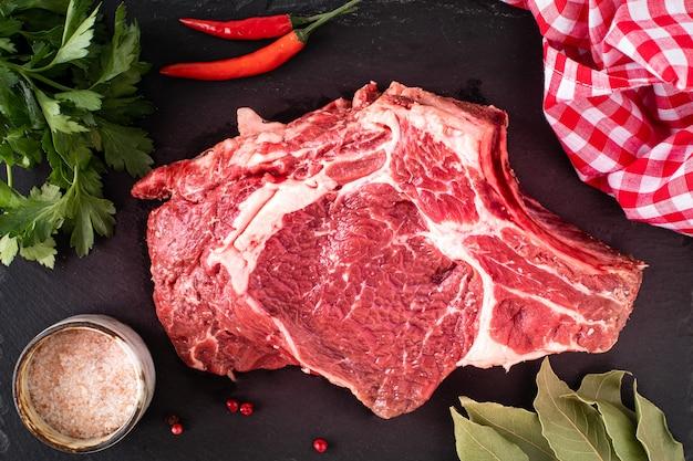 Rohes saftiges fleischsteak bereit zum grillen auf einem schwarzen schieferbrett. steak mit knochen, kalbfleisch auf einem holzbrett mit kirschtomaten, peperoni und kräutern. ansicht von oben Premium Fotos