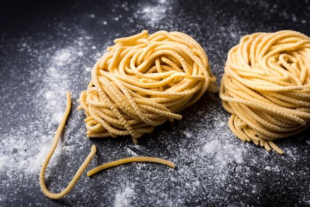 Rohes selbst gemachtes capellini-teigwarennest mit mehl auf einem schwarzen hintergrund Kostenlose Fotos