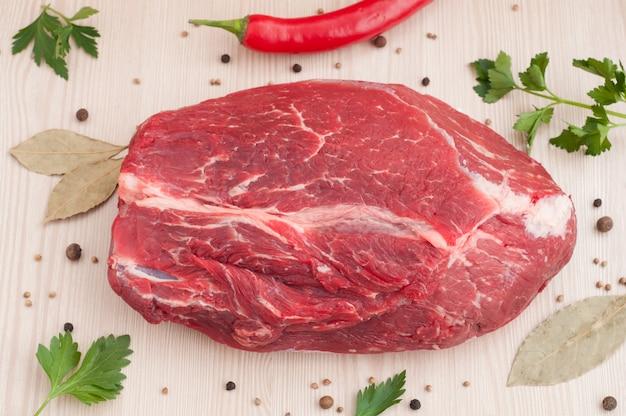 Rohes stück rindfleisch mit gewürzen und petersilie auf dem tisch Premium Fotos