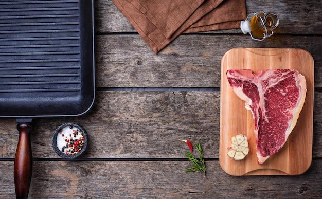 Rohes t-bone-steak und grillpfanne aus eisen Premium Fotos
