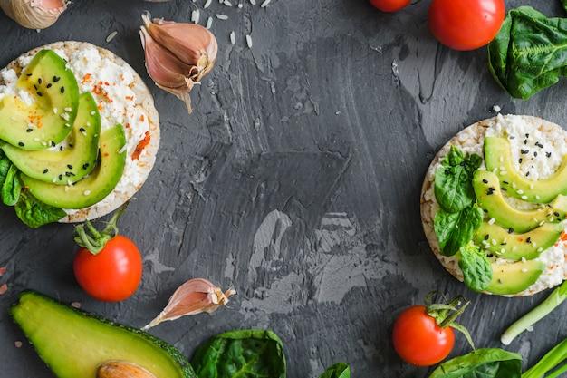 Rohwaren mit avocado; frischkäse und reiskuchen über strukturiertem hintergrund Kostenlose Fotos