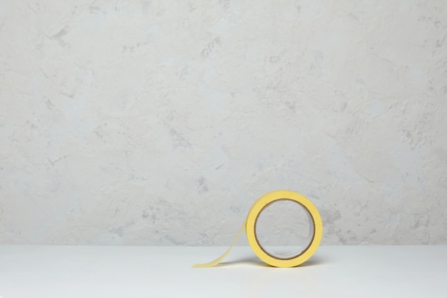 Rolle des gelben papierabdeckbandes auf holztisch Premium Fotos