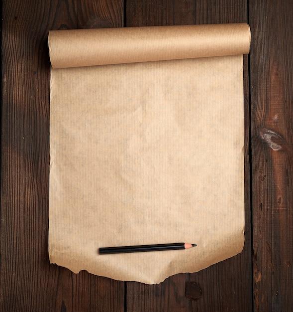 Rolle des ungedrehten braunen papiers auf einer holzoberfläche von den alten brettern Premium Fotos