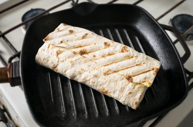 Rolle von pita-brot in einer pfanne. Premium Fotos