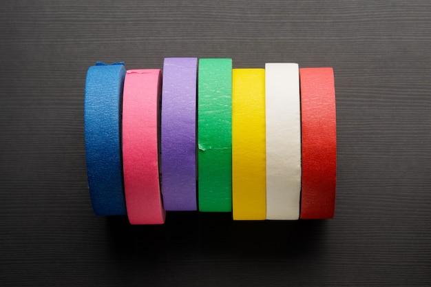 Rollen des farbigen abdeckbandes auf dunklem holzhintergrund. draufsicht. Premium Fotos
