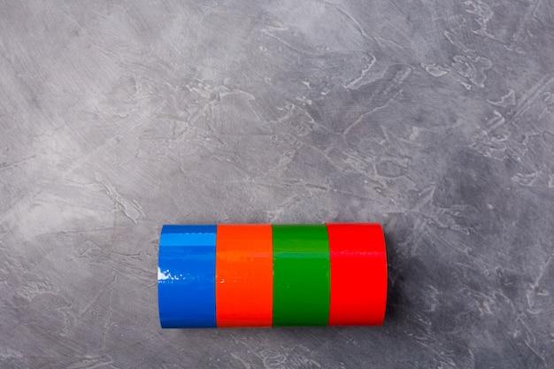 Rollen des farbigen klebebandes auf grauem hintergrund. freiraum. speicherplatz kopieren. Premium Fotos