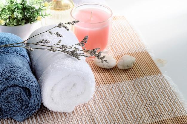 Rollen sie oben von den sauberen tüchern auf weißer tabelle mit kerze und houseplant, kopienraum. Premium Fotos