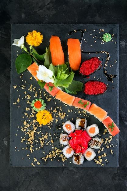 Rollen und sushi auf einem schwarzen schieferhintergrund, japanische küche Premium Fotos