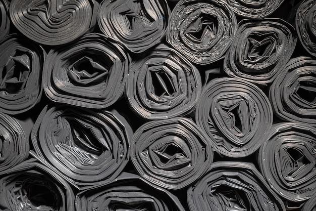 Rollen von plastiktüten. strukturierter hintergrund. viele schwarze aufgerollte taschen für bauschutt. Premium Fotos