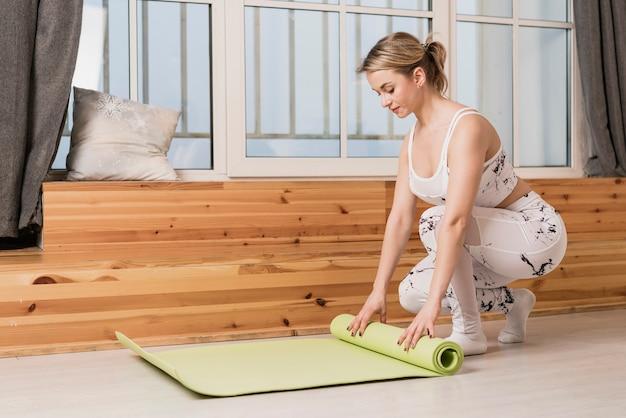 Rollende yogamatte der hohen winkelfrau Kostenlose Fotos