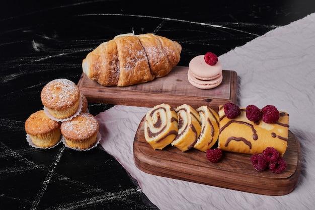 Rollkuchen mit beeren auf einer platte mit muffins. Kostenlose Fotos