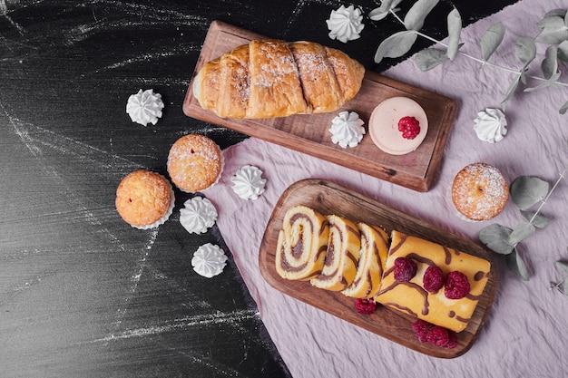 Rollkuchen mit himbeeren auf einer platte mit muffins. Kostenlose Fotos