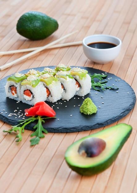 Rolls mit avocado auf einem bambushintergrund. Premium Fotos