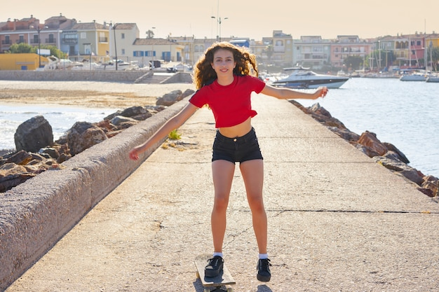 Rollschuhmädchen in einem stranddock mit rot Premium Fotos