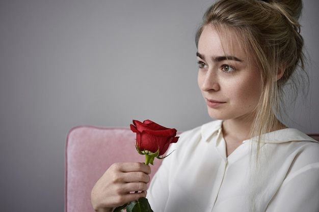 Romantik, liebe und natürliches schönheitskonzept. schließen sie herauf beschnittene ansicht der schönen romantischen jungen frau mit hellem haar, das weiße bluse trägt, die lokal sitzt und rote rose am valentinstag riecht Kostenlose Fotos