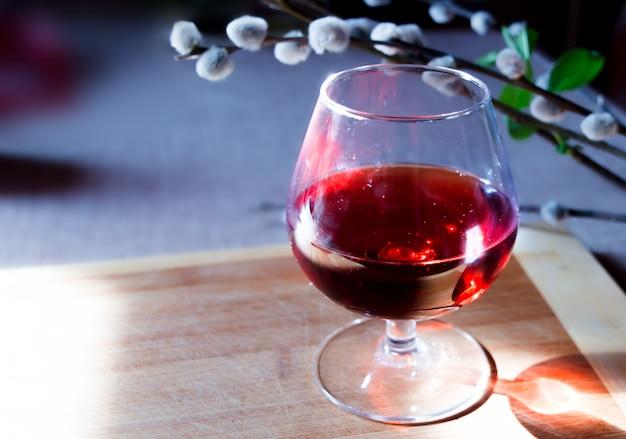 Romantische ansicht mit einem glas wein und einer weidenniederlassung auf einem hölzernen brett. Premium Fotos