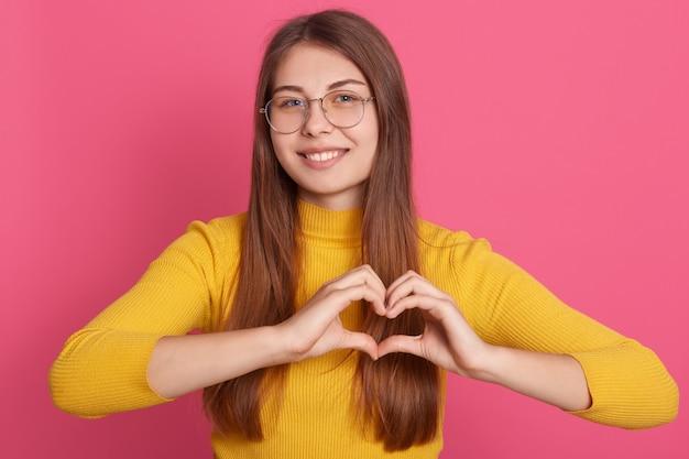 Romantische dame kleidet gelbes freizeithemd, das symbol des herzens mit ihren händen macht, frau macht liebeszeichen mit den fingern Kostenlose Fotos