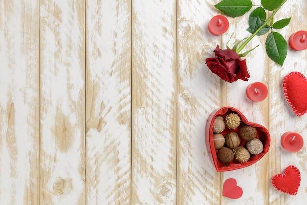 Romantische dekoration des valentinstags mit rosen und schokolade auf einem weißen holztischhintergrund Premium Fotos